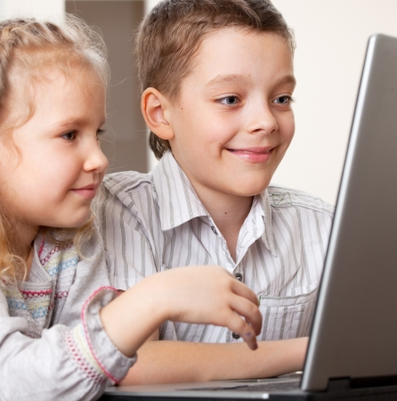 Children with laptop indoors. Happy kids playing computer at home. photo