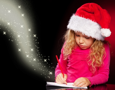 Child writing a magic letter to santa claus. Little girl  photo