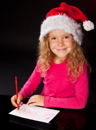 Child writing a letter to santa claus. Little girl photo