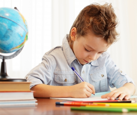 homework: Little boy does house lessons Stock Photo