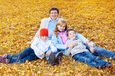 Family in autumn park. Mother, fatherr and children outdoors photo