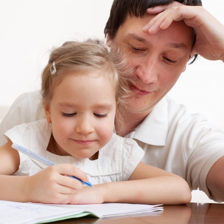 two parents: Father helping daughter doing homework. Parent with child writing Stock Photo