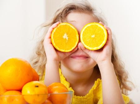 orange slice: Kind met sinaasappelen. Gelukkig meisje met fruit in huis. Stockfoto