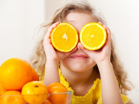 frutas divertidas: Ni�o con las naranjas. Ni�a feliz con la fruta en casa. Foto de archivo