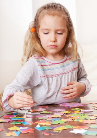 learning by doing: Child playing puzzle. Little girl play at home
