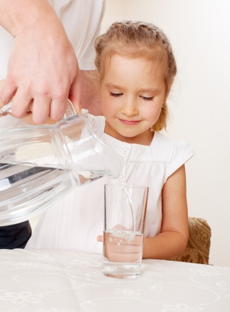 carafe: Child with glass pitcher water. Little girl drinking water at home