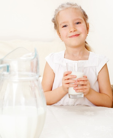 Child with glass pitcher milk. Little girl drinking milk for breakfast photo