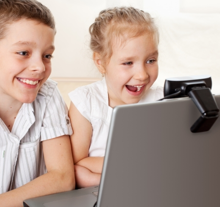 �hildren communicate with online. Happy kids with laptop at home photo