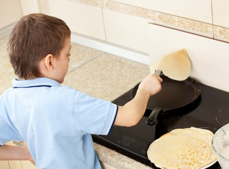 griddle: Child bakes pancakes in the kitchen. Boy cooking breakfast Stock Photo