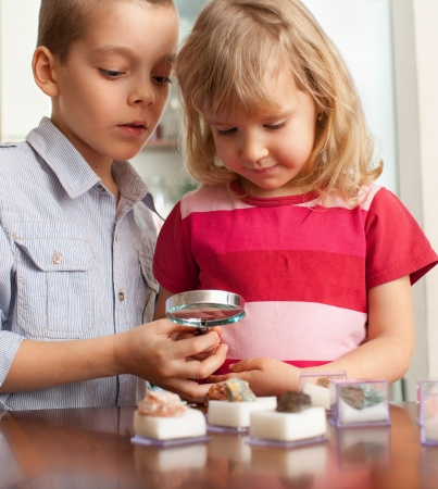 Children are considering a magnifying glass collection of stones Stock Photo - 14698072
