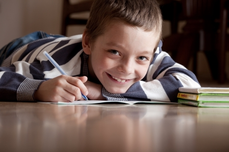 Child does lessons lying on the floor Stock Photo - 14698069
