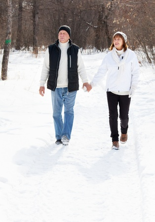 Happy seniors couple walking in winter park. Elderly mature people photo