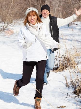 Happy seniors couple in winter park. Elderly mature people