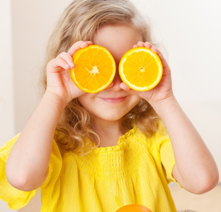 children breakfast: Childr with oranges. Happy little girl with fruit at home.