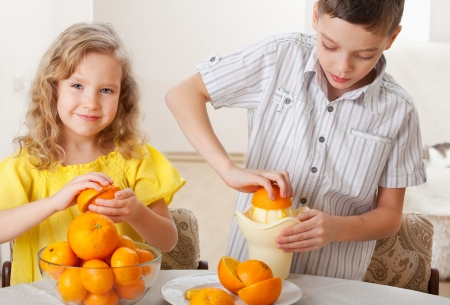 2 persons only: Children with oranges. Happy little girl and boy squeezed fresh juice.