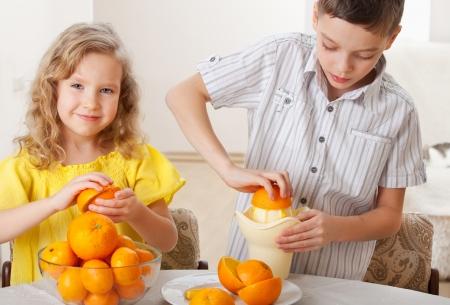 naranjas: Los niños con naranjas. Niña feliz y el niño exprimido jugo fresco.