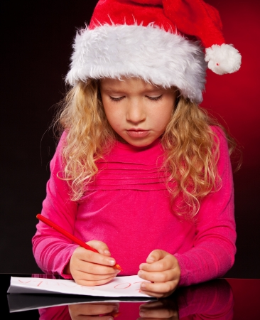 Child writing a letter to Santa Claus. Little girl in christmas hat on black background photo
