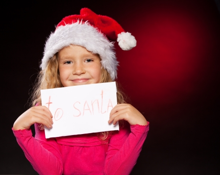 Child with letter to Santa Claus. Little girl in christmas hat on black background photo