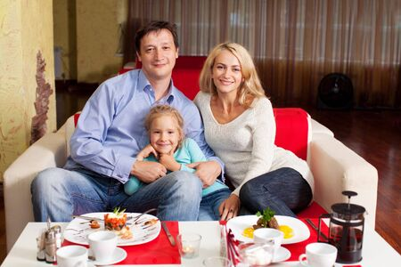 Happy family eating in cafe photo
