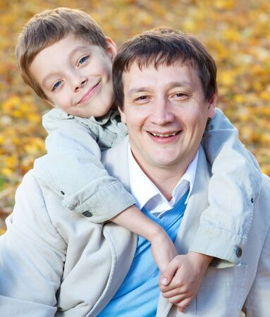 Father with son in autumn park photo