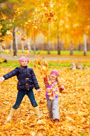 Happy children in autumn park. Kids juggle leaves photo