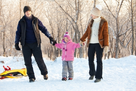 Family walking in a winter park. Parents with child on sled photo