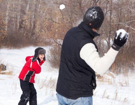 ropa de invierno: Familia jugando bola de nieve. Padre con el hijo de caminar en Winter Park