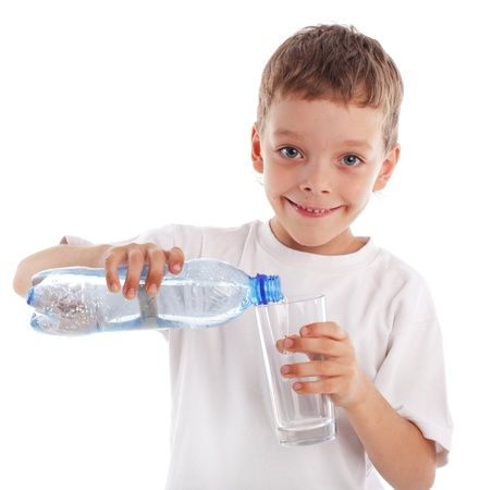 Child pouring water in a glass isolated on white photo