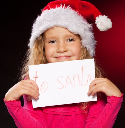 Child with letter to Santa Claus. Little girl in christmas hat on black background Stock Photo - 15530113
