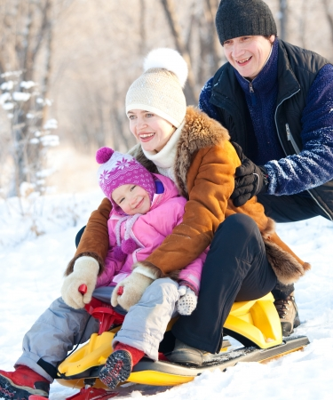 Family sledding in a winter park. Parents with child on sled photo