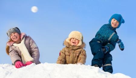 bolas de nieve: Ni�os en invierno. Felices los ni�os jugando bola de nieve Foto de archivo