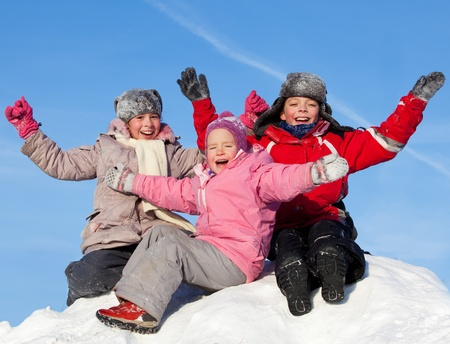 Happy kids on snow. Children against the sky in winter.  photo