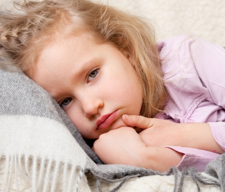 sick person: Illness child. Little girl wrapped in a blanket Stock Photo