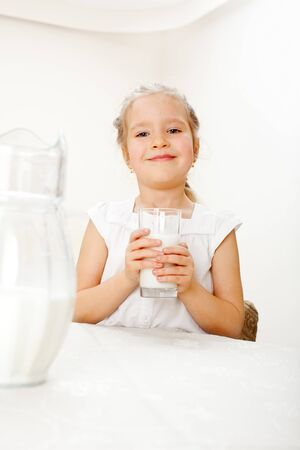 replenishment: Child with glass pitcher milk. Little girl drinking milk for breakfast Stock Photo