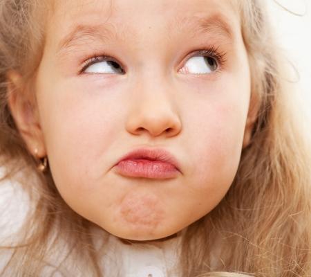 grimacing: Grimacing child. Nescience little girl. Stock Photo
