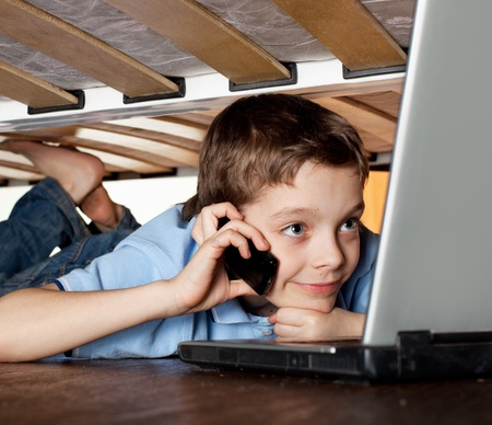 dependent: Child playing laptop under the bed. Computer Addiction Stock Photo