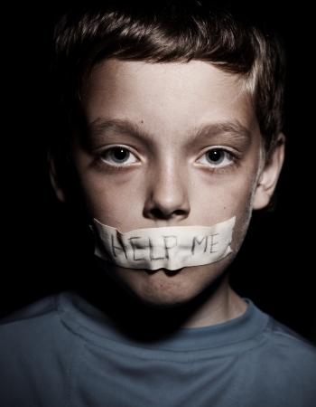 Teen with taped mouth, begging for help. Sad, abuse boy. Violence, despair. Stock Photo