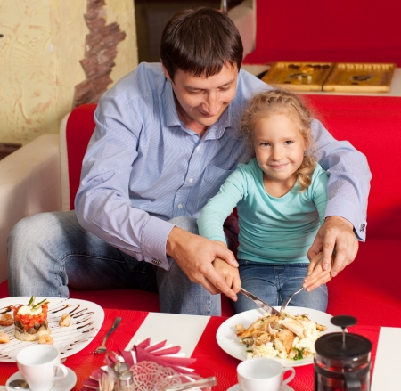 a little dinner: Happy family eating in cafe Stock Photo