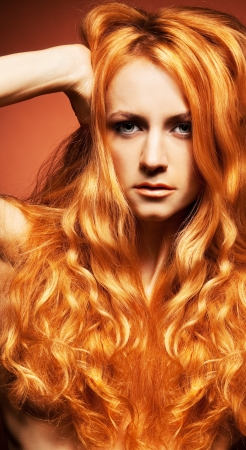 young naked girl: Fashion portrait of redhead woman with long hair on brown background