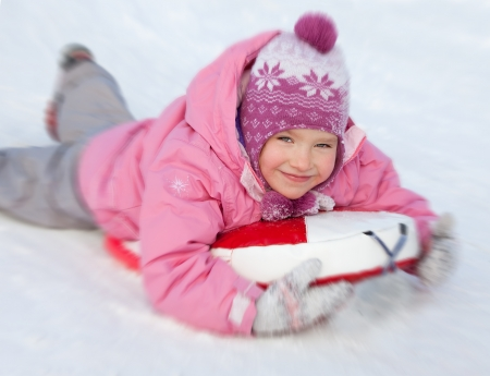 Happy child on sledge in winter photo