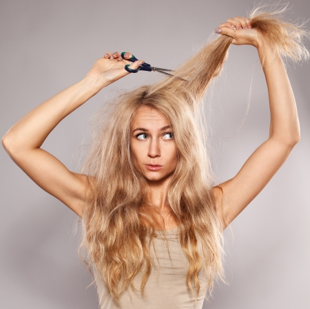 hair cut: Young woman looking at split ends. Damaged long hair