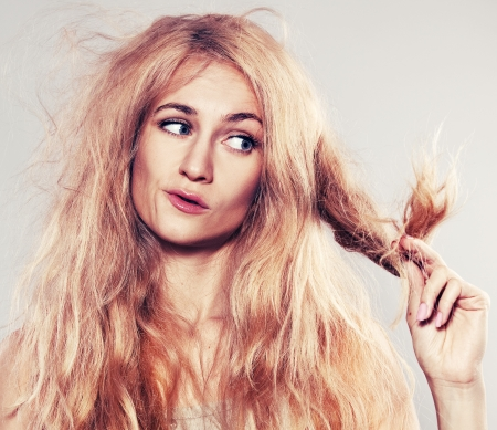 problem health: Young woman looking at split ends. Damaged long hair