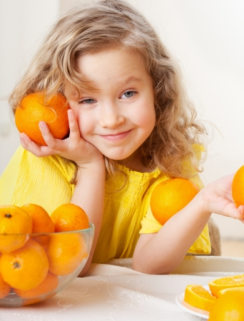 mandarin oranges: Child with oranges. Happy little girl with fruit at home.