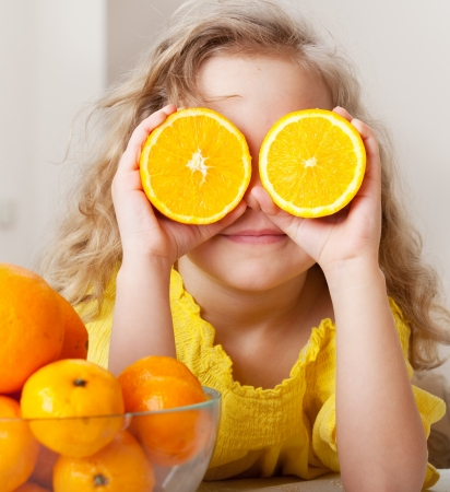 kids eating healthy: Child with oranges. Happy little girl with fruit at home.