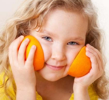 naranjas: Niño con las naranjas. Niña feliz con la fruta en casa. Foto de archivo