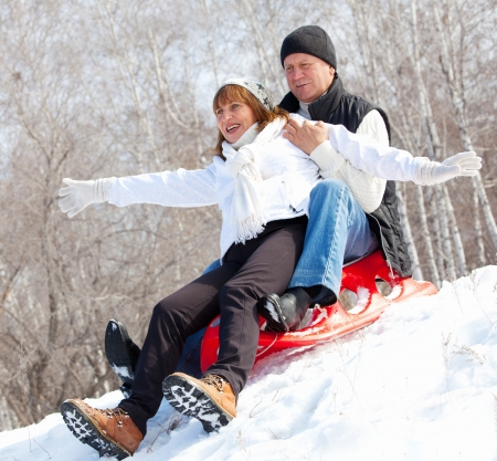 Mature couple sledding. Seniors couple on sled in winter park photo