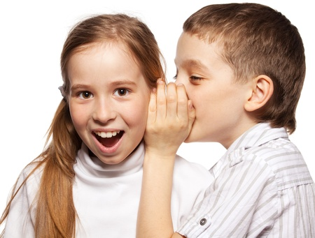 brother and sister: Boy whispers girl in the ear secret. Childrens gossip