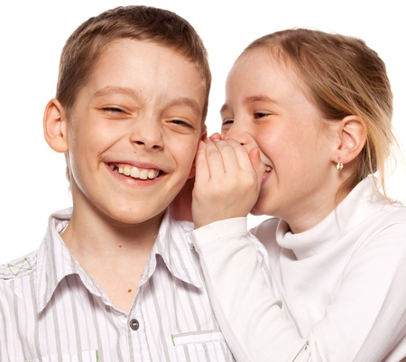Girl whispers boy in the ear secret. Childrens gossip photo