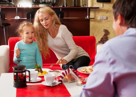 Happy family eating in restaurant. Mother, Father and child in cafe Stock Photo