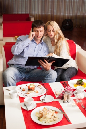 Young couple sitting in cafe. Man and woman in restaurant choose menu photo